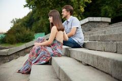 Пары сидя на лестницах на зеленой предпосылке Стоковые Изображения RF