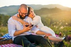 Пары сидя на одеяле пикника с бокалами Стоковое Фото