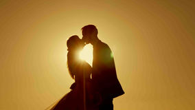 Пары силуэта целуя над предпосылкой захода солнца Стоковые Фотографии RF