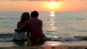 Пары сидят на пляже сток-видео