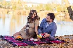 Пары сидят около озера, времени осени Стоковое Фото