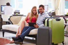 Пары сидя в лобби гостиницы смотря таблетку цифров Стоковое фото RF