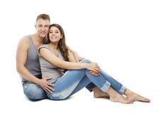 Пары сидя над белой предпосылкой, счастливыми молодыми взрослыми людьми стоковые фото