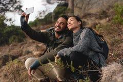 Пары сидя на горной тропе и принимая selfie Стоковое Фото