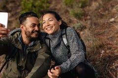 Пары сидя на горной тропе принимая selfie Стоковое Изображение RF