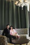 Пары сидя на кресле в лобби гостиницы Стоковая Фотография RF