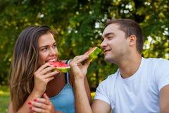 Пары сидя на одеяле пикника и есть арбуз Стоковое Изображение