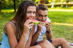 Пары сидя на одеяле пикника и есть арбуз Стоковое Фото