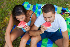 Пары сидя на одеяле пикника и есть арбуз Стоковая Фотография