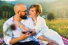 Пары сидя на одеяле пикника с бокалами Стоковые Изображения