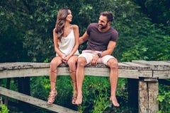 Пары сидя на пристани и смеяться над Стоковая Фотография