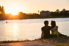 Пары сидя на речном береге на заходе солнца Стоковое фото RF