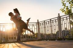 Пары сидя на речном береге на заходе солнца Стоковая Фотография