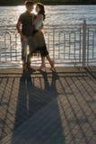 Пары сидя на речном береге на заходе солнца Стоковые Фотографии RF