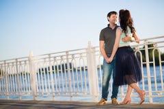 Пары сидя на речном береге на заходе солнца Стоковое Фото