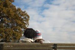 Пары сидя на скамейке в парке Стоковые Фотографии RF