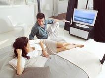 Пары сидя на софе и смотря ТВ Стоковые Изображения