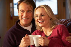 Пары сидя на софе при горячие пить миря TV Стоковое фото RF
