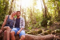Пары сидя на стволе дерева в лесе совместно Стоковые Изображения RF