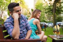 Пары сидя на стенде и смеяться над Стоковая Фотография RF