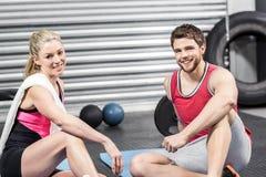 Пары сидя на циновке фитнеса Стоковые Фотографии RF