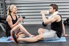 Пары сидя на циновке фитнеса Стоковая Фотография RF