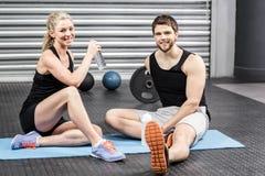 Пары сидя на циновке фитнеса Стоковое Фото