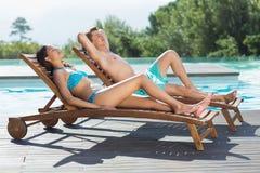 Пары сидя на loungers солнца бассейном Стоковые Фото