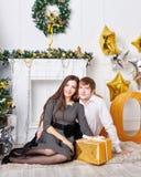 Пары сидя рядом с рождественской елкой и настоящими моментами Стоковые Изображения RF