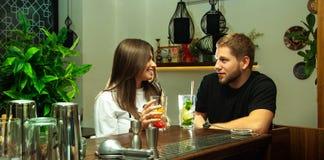 Пары сидя с коктеилями на баре Стоковое Изображение