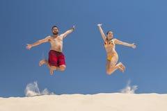 Пары скача на пляж Стоковое Фото