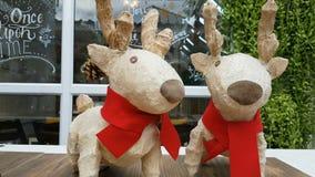 Пары скульптуры северного оленя с красным шарфом как украшение с коммерчески магазином на предпосылке акции видеоматериалы