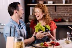 Пары смеясь над и варя овощами Стоковое Фото