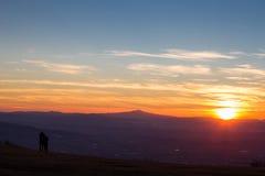 пары смотря заход солнца Стоковые Изображения RF