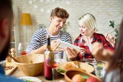 Пары смотря используя таблетку цифров на обедающем Стоковые Фото