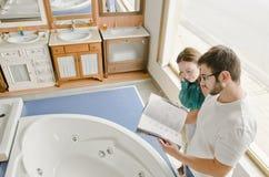 Пары смотря каталог в магазине ванны Стоковая Фотография RF