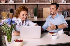 Пары смотря компьтер-книжку пока имеющ завтрак Стоковое Фото