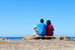 Пары смотря на море в старой стыковке Стоковые Изображения