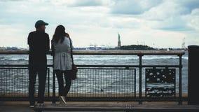 Пары смотря статую свободы стоковые изображения