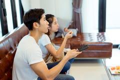 Пары совместно смотря телевидение в комнате стоковое изображение
