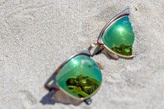 Пары солнечных очков на пляже с отражением красивого Стоковое фото RF