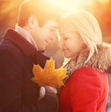 Пары солнечного портрета счастливые молодые усмехаясь влюбленн в кленовый лист осени outdoors на теплом заходе солнца Стоковые Фотографии RF