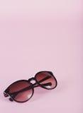 Пары солнечных очков женщин на редкой розовой предпосылке Стоковое Изображение