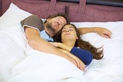Пары спать в обнятой кровати ослабленной Стоковое фото RF
