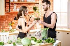 Пары спорт есть здоровую еду на кухне дома стоковые изображения