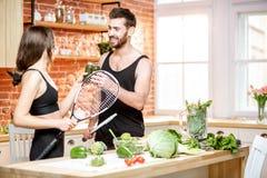 Пары спорт есть здоровую еду на кухне дома стоковое изображение rf