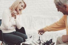 Пары старые люди играя шахмат дома стоковые изображения rf