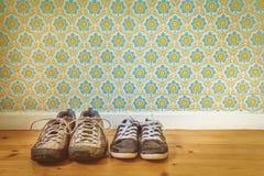 2 пары старых пакостных ботинок перед ретро обоями Стоковая Фотография RF