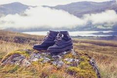Пары старых черных сапогов для походов на утесе в горах стоковое фото