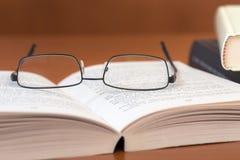 Пары стекел на учебнике на деревянной предпосылке Стоковое фото RF